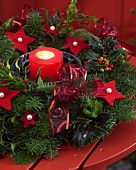 Advent wreath with candle and red felt stars on wooden table