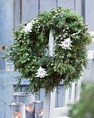 Winter wreath of juniper with Christmas-tree-shaped decorations on terrace