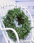 Winter wreath of juniper on white wicker chair on terrace