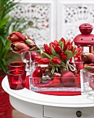Red Christmas arrangement of tulips, amaryllis and baubles