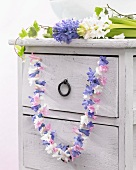 Vintage chest of drawers decorated with garland of hyacinth florets