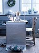 Gedeckter Tisch im Silberlook - Brennende Kerzen vor Gläser und Teller auf Tischläufer aus silbernem Papier und Vintage Holzstühle am Tisch