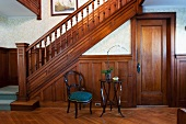 Baroque chair next to modern side table in front of half-height wood panelling on wall of wooden staircase in traditional hallway