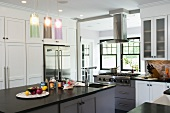 Free-standing kitchen island below modern pendant lamps with coloured glass shades in white country-house kitchen