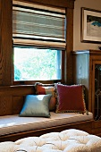 Cushions on built-in window seat at window with half-open blind