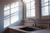 Old sink below window next to pattern of light and shadow on wall