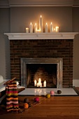 Candlelit fireplace with knitting and balls of wool on floor