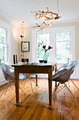 Rustic wooden dining table and pale grey plastic shell chairs below pendant lamp crafted from roots