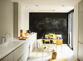 Restrained, modern kitchen counter with Corian counter top and colorful dining area in front of a chalkboard wall