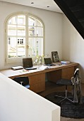 Behind the stair balustrade a custom home office with an arch window above a streamlined desk with wooden base cabinets