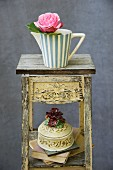 Rose in a pitcher on a vintage stool