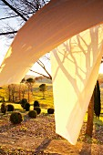 Pergola with wafting curtain and patterns of light and shadow in front of Mediterranean landscape