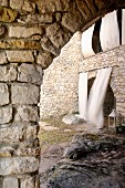 View through stone arch into courtyard with arched doorway and balcony with white curtains