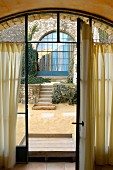 View through open French window into courtyard terrace with blue, arched lattice window on far side