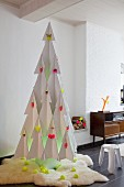 Stylised Christmas tree made from white cardboard with decorations in neon yellow and pink on white fur rug