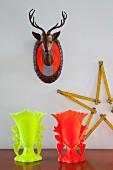 Hirschbüste mit Sicherheitsstreifen, zu Stern geformter Zollstock und festliche Kelche in Neonfarben