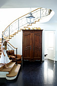 Spacious staircase with playful, wrought iron banister and antique wooden armoire in the lobby of a town home