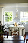 White, lacquer country kitchen with vintage look kitchen cabinets; natural wood dining area in the foreground