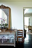 Orchideen und goldgerahmter Spiegel auf altem Holztisch, daneben Blick ins Wohnzimmer mit traditionellen Polstersesseln