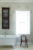 Traditional bathroom with glass-fronted wall cabinet above retro bathtub and classic bentwood chair; window with interior shutters