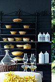 Ceramic containers and white porcelain containers on shelves in front of a black, patio wall
