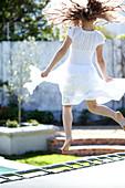 Girl wearing romantic, white summer dress jumping on trampoline in garden