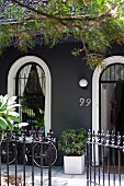 Elegant house with dark grey facade and open, wrought iron garden gate