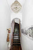 Chandelier on ceiling of narrow hallway with gallery of photos on wall in front of arched doorway and staircase in grand apartment