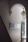 View through arched doorway of chandelier and gallery of photos on wall of narrow hallway of grand apartment