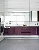 Long washstand counter and strip of mirrors on white wall tiles
