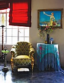 Upholstered armchair with gilt legs, side table draped with fringed cloth and modern, red Roman blinds in front of glazed windows