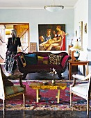 Interior in eclectic mixture of styles with antique seating and collection of unusual objet; woman leaning on sofa