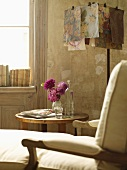 Detail of chaise longue, lamp and vase of flowers on table and backlit books on window sill