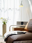 Woollen blanket, newspaper and iPad on leather couch, iPod dock on wooden block table, standard lamp, vase of flowers and backlit curtains at window