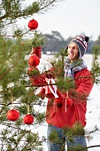 Man decorating Christmas tree in woodland