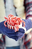 Hands holding mug of candy canes