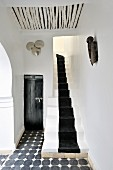 Fusion of Moroccan tradition and modern elements in foyer decorated in black and white with narrow staircase