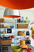 Orange industrial lamps and metal shelving in simple kitchen with colourful utensils