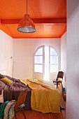 Simple industrial style in narrow bedroom with ceiling painted a bold orange