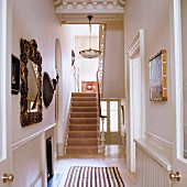 Victorian entry hall - view of a narrow hallway with decorative objects on the wall and antique hanging light on the plaster ceiling above the stairway