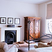 Partially obscured view of a bed with wrought iron frame across from an open fireplace and Biedermeier armoire in an elegant bedroom