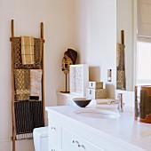 Modern, white bathroon vanity next to a ladder towel rack and patterned hand towels
