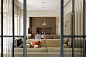 View though half-open, glass sliding doors into lounge area with pale sofa set and dining area against brick wall