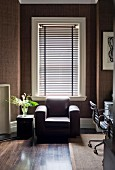 Chunky brown leather armchair in front of window with louver blind in study with dark brown fabric wallpaper