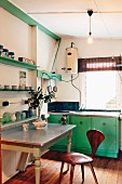 Vintage kitchen with the wood components painted green and bentwood chair at an antique table with stainless steel top