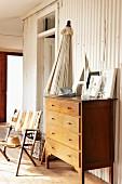Zusammengeklappter Sonnenschirm, Holzkommode und stoffbespannter Gartenstuhl vor Wandverkleidung aus weißem Profilblech