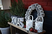 Christmas arrangement on terrace: lanterns, decorative letters, wreath of pine cones, small potted conifers