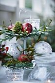 Weihnachtsgesteck auf einer Etagere mit Äpfeln, Tannenzweigen, Misteln, Moos, Windlicht und Christbaumkugeln