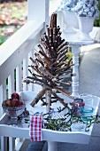 Weihnachtsdeko auf einem Terrassentischchen: Christbaum aus Zweigen, Äpfel, Mistelzweige
