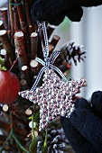 Decorating a Christmas tree made of twigs with ornaments